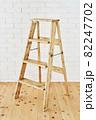 白いレンガの壁の前に置かれたアンティークな木製脚立 82247702
