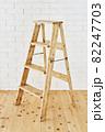 白いレンガの壁の前に置かれたアンティークな木製脚立 82247703