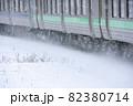 雪中で雪を巻き上げて走る電車 82380714