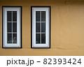 オレンジ色の壁と二つの窓 82393424
