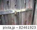 古い木製の扉の閂に付けられた錠前 82461923