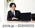 ノートパソコンで営業をするスーツ姿のビジネスマンの若い男性 82640050
