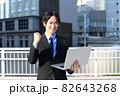 街中でノートパソコンを持つスーツ姿の笑顔の若い男性 82643268