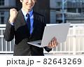 街中でノートパソコンを持つスーツ姿の笑顔の若い男性 82643269