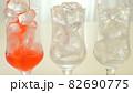 苺のかき氷シロップを氷の入ったグラスに注ぐ様子 82690775