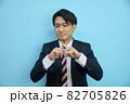 青背景の前でバツを作る日本人ビジネスマン 82705826