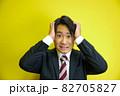 頭に手を当ててショックを受ける日本人男性 82705827