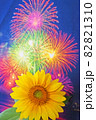 夏の夜空にパッと咲いた大輪の花火とひまわり 82821310