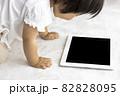寝転がって、タブレット端末を使う赤ちゃんのイメージ(1歳2か月、日本人、女の子) 82828095