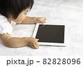 寝転がって、タブレット端末を使う赤ちゃんのイメージ(1歳2か月、日本人、女の子) 82828096