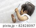 寝転がって、タブレット端末を使う赤ちゃんのイメージ(1歳2か月、日本人、女の子) 82828097