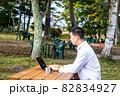 長野県の自然公園の中でノマドワークをする男性 82834927