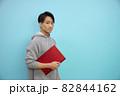 ノートパソコンをもつ灰色パーカーの日本人男性 82844162