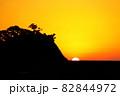沈む夕日と岩場のシルエット 82844972