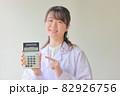 電卓を指さす白衣の笑顔の女性1 82926756
