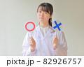 〇とXのプレートを持ち困った表情の白衣女性1 82926757