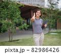 woman walking with laptop in modern park street 82986426
