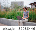 woman working with laptop in modern university campus park. 82986446