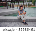 Portrait of young woman in park with smartphone 82986461
