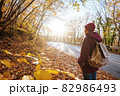 Lonely Woman Walking Away into the Autumn Forest 82986493