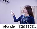 リモコンでエアコンの調節をする日本人女性 82988781