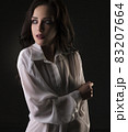 Sexy brunette in shirt cropped view in dark room 83207664
