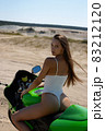Tempting woman sitting on modern motorbike on seashore 83212120