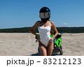 Seductive woman in swimsuit near motorbike on beach 83212123