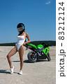 Seductive woman in swimsuit near motorbike on beach 83212124