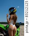 Seductive woman in swimsuit near motorbike on beach 83212125