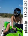 Alluring fit woman in helmet sitting on motorbike on beach 83212129