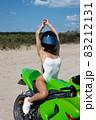 Alluring fit woman in helmet sitting on motorbike on beach 83212131
