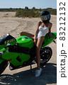 Alluring fit woman in helmet sitting on motorbike on beach 83212132