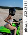 Alluring fit woman in helmet sitting on motorbike on beach 83212134