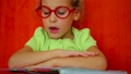 Little girl in red glasses reads book aloud against red wall 7889019