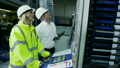 Mature factory manager shows his staff how to operate machinery 10586753