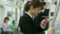 電車内でスマホを操作する女性 14113031