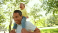 Smiling dad carrying his happy little girl on his shoulders 14948029