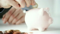 close up of man putting coins into piggy bank 16238064