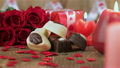 Red roses and chocolate candies with candles on wo 19974604