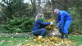 People pick leaves in autumnal park. 20937574