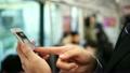ビジネスマン 通勤 スマホ 電車内 車内の広告(窓上ポスター)を見てスマホで調べる 納得 21014427
