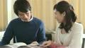 カタログを見ながら話す若い夫婦 21421889
