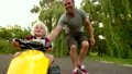Happy dad pushing his laughing child in a toy car 22394873