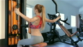 Woman sits backwards on the bench of gym machine 23444742