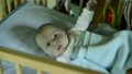 Cute little baby boy lying in wooden crib, moving, 23550545