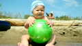 Cute baby boy playing with a ball on the beach 23993359
