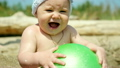 Cute baby boy playing with a ball on the beach 23993385