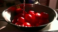 Pouring water over red tomatoes in a pan. Super 24331664