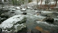 Rushing stream crashes over snow-covered boulders 24441153